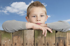 Little boy looking from bove a fence Stock Image