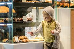 Little boy is looking at the buns. stock image