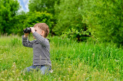 Little boy looking at the camera with binoculars Stock Photography