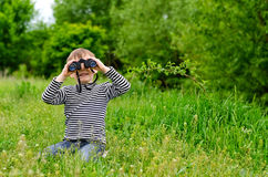 Little boy looking at the camera with binoculars Stock Image