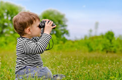 Little boy looking at the camera with binoculars Royalty Free Stock Images
