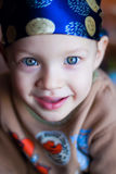Little boy looking at the camera, blue eyes bright in the bandana royalty free stock images