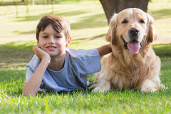Little boy looking at camera with his dog in the park Stock Images