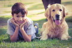 Little boy looking at camera with his dog in the park Stock Photography