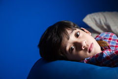 Little boy looking into the camera. Little kid lying on a blue couch looking into the camera Stock Photos