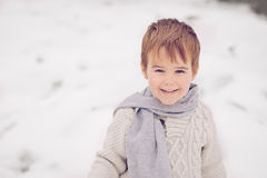 Little boy looking at the camera, laughing. Boy wearing scarf and sweater laughing and looking kind in winter snow Stock Photography