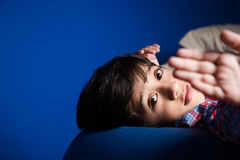 Little boy looking into the camera with one hand in front. Royalty Free Stock Photos