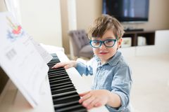 Toddler boy playing piano stock image