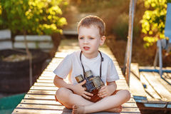 Little boy looking through camouflage binoculars on river bank Royalty Free Stock Photo