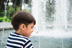 Little boy looking at fountain in the park summer time Stock Photos