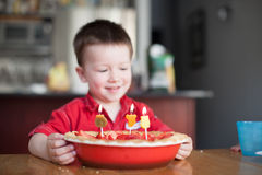 Little boy looking at his birthday cake with Royalty Free Stock Photography