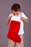 Little boy looking in his Christmas stocking Royalty Free Stock Photos
