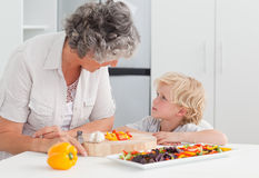 Little boy looking at his grandmother cooking. At home Stock Photo