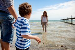 Little Boy Looking at His Mom Dipping in the Water Stock Photo