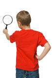 Little boy looking through the magnifying glass Stock Photo