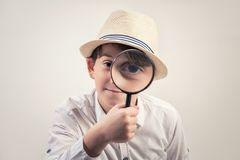 Little boy looking through a magnifying glass against grey background. Little boy looking through a magnifying glass against grey background royalty free stock image