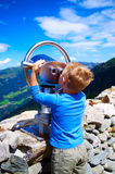 Little boy looking at the mountains through telescope. Boy watching the mountains through telescope at Austria Alps Stock Photography