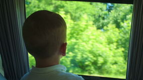 Little boy looking out the open bus window during stock footage