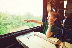 Little boy looking out train window. Kid pointing outside from train window. Family vacations and traveling by railway in summer. Family adventure by train royalty free stock photos