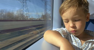Little boy looking out train window on sunny day stock video footage