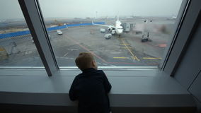 Little boy looking out the window at airport stock video footage