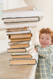 Little boy looking at pile of books, focus on foreground Royalty Free Stock Photography