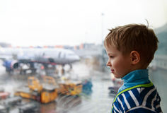 Little boy looking at planes in the airport. Kids travel Stock Photos
