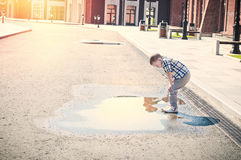 Little boy is looking at the puddle Stock Image