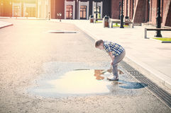 Little boy is looking at the puddle Stock Photography