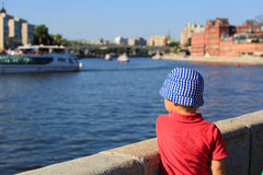 Little boy looking at the quay in city. Little boy looking at the quay in summer city Stock Photos