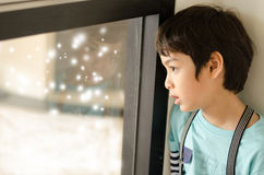 Little boy looking at snow outside of window Stock Image