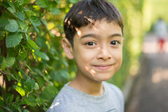 Little boy looking straight to the camera in front of tree fence Royalty Free Stock Images