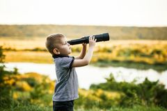 Little boy looking into telescope eyepiece. Little blond boy looking in a large pair of binoculars. Park in the background Stock Photo