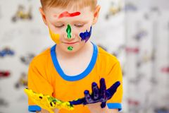 Little boy looking to his painted hands Royalty Free Stock Images