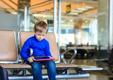 Little boy looking at touch pad in the airport Stock Images