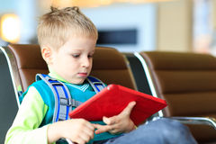 Little boy looking at touch pad in the airport Royalty Free Stock Image