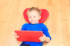 Little boy looking at touch pad, early learning Stock Image