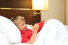 Little boy looking at touch pad in hotel room Stock Photography