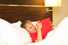 Little boy looking at touch pad lying in bed of Royalty Free Stock Image