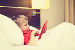 Little boy looking at touch pad lying in bed of Stock Photo
