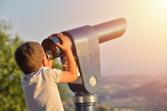 Little boy looking into tourist telescope eyepiece. Travel touri. St destination landscape magnification Royalty Free Stock Photos