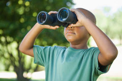 Little boy looking up through binoculars in the park Stock Images