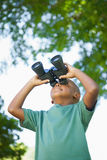 Little boy looking up through binoculars in the park Stock Photo