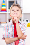 Little boy looking up. Happy smiling young boy looking up. Child in the classroom or home Royalty Free Stock Images