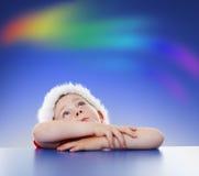 Little boy looking up to rainbow on sky Stock Photo