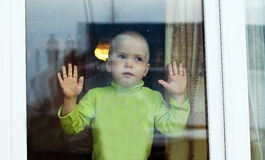 Little boy looking at the window royalty free stock image