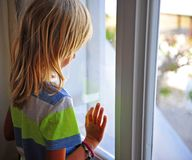 Little boy looking at window royalty free stock photo