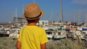 Little boy is looking on the yacht port. Little boy in a straw hat is looking on the yacht port stock footage