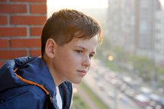 A little boy looks from the balcony stock photography