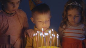 A little boy looks at candles on a festive cake and makes a wish stock video footage
